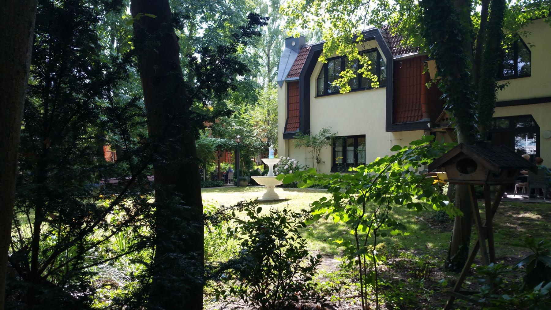 Durch die Bäume mit Blick auf Brunnen und Haus