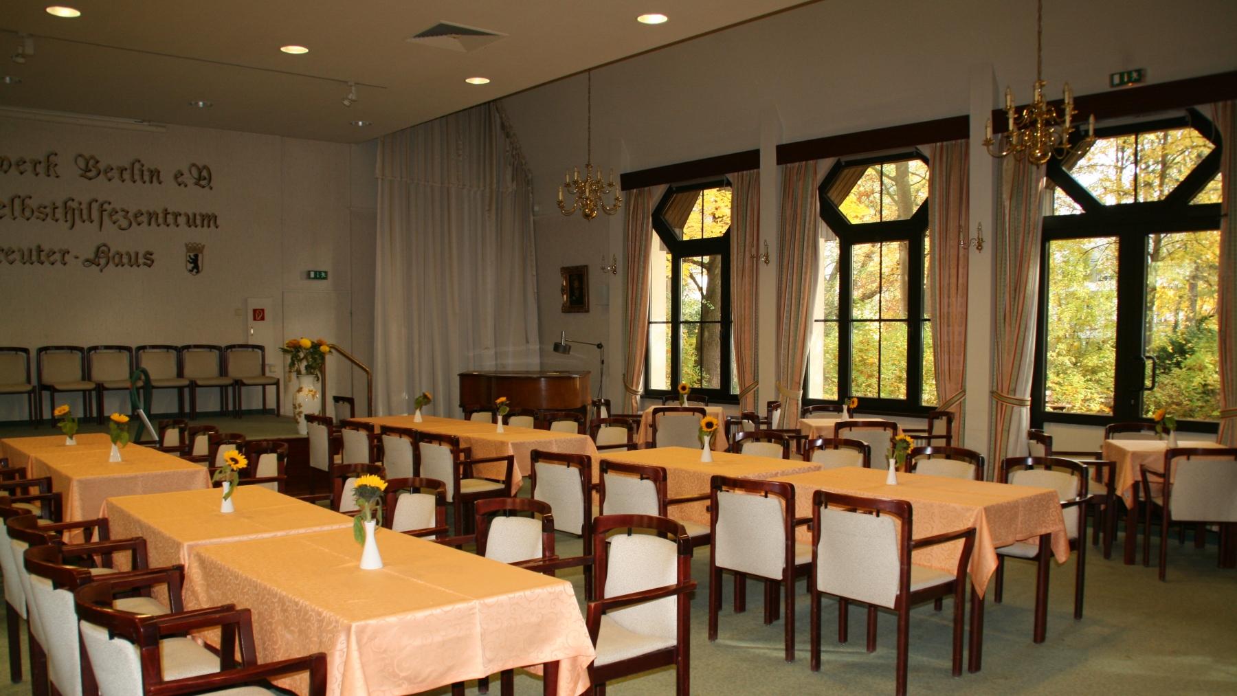 Veranstaltungssaal mit Tischen und Stühlen; Blick auf Bühne